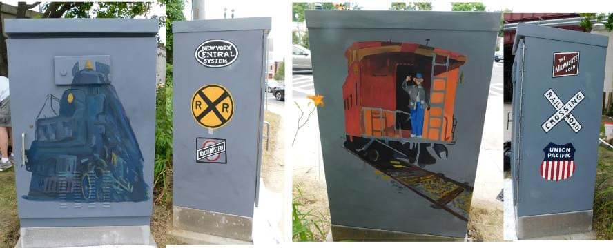 Finished painting of electrical box with train art, engine, caboose and signs