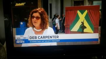 Television screenshot of spectrum news broadcast with interview with Deb Carpenter with painted electrical box in the background