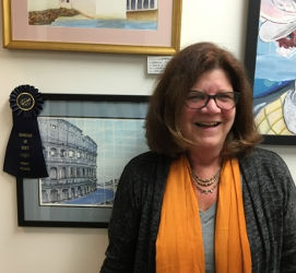 Deb Carpenter standing in front of her 1st place painting