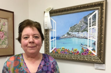 Joyce Jackson standing in front of her 3rd place painting