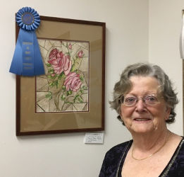 Lilian Walsh standing in front of her honorable mention painting