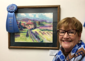 Carole Warburton standing in front of her honorable mention painting