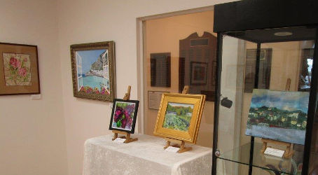 artist paintings on the museum wall, two on a table and one in a glass case