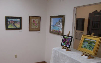 artist paintings on the museum wall, two on a table