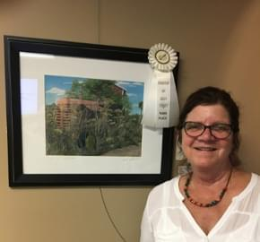 Deb Carpenter standing in front of her 3rd place painting